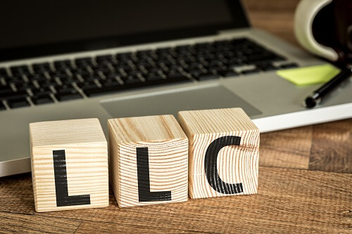 LLC wooden building blocks with a business laptop in the background